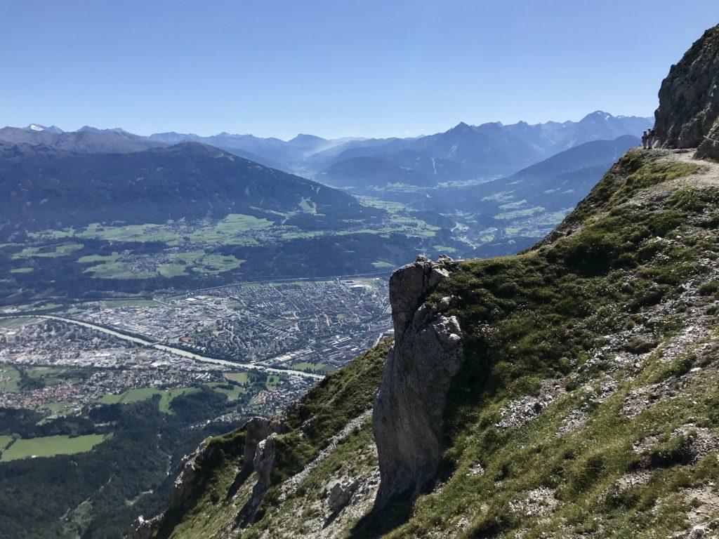 Auf dem Goetheweg im Karwendel wandern - links unten die Stadt Innsbruck, rechts der Weg mit den Wanderern