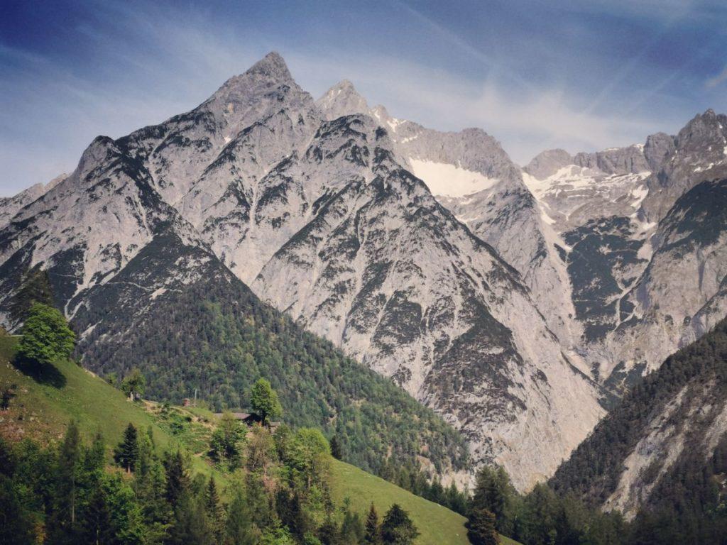 Einmalig schön: Die grüne Almwiese rund um die Alm, dahinter die schroffen Spitzen des Karwendel